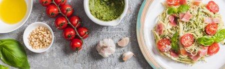 Foto de Vista superior de Pappardelle cocido con tomates, albahaca y jamón cerca de los ingredientes en la superficie gris, plano panorámico - Imagen libre de derechos