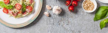 Photo pour Top vue de Pappardelle cuite avec tomates, basilic et prosciutto près des ingrédients sur surface grise, grenaille panoramique - image libre de droit