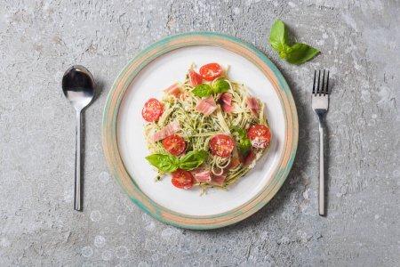 Photo pour Top vue de Pappardelle cuite avec tomates, basilic et prosciutto près de la coutellerie sur surface grise - image libre de droit