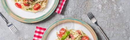 Photo for Top view of Pappardelle with tomatoes, basil and prosciutto on plates on plaid napkins with forks on grey surface, panoramic shot - Royalty Free Image