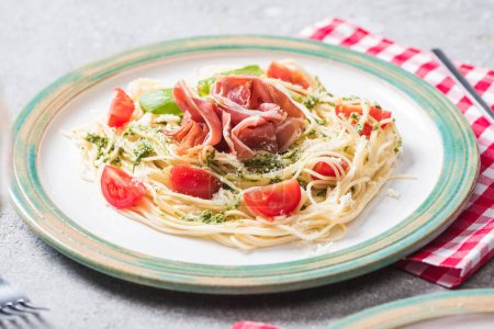 Photo for Pappardelle with tomatoes, basil and prosciutto on grey surface with plaid napkin - Royalty Free Image