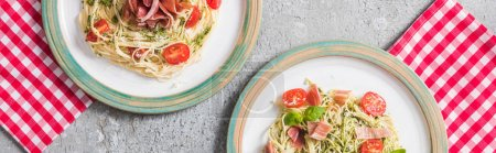 top view of served Pappardelle with tomatoes, basil and prosciutto on plaid napkins on grey surface, panoramic shot