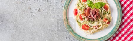 top view of served Pappardelle with tomatoes, basil and prosciutto on plaid napkin on grey surface, panoramic shot