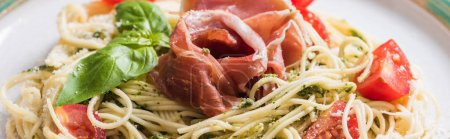 Photo pour Close up view of cooked Pappardelle with tomatoes, basil and prosciutto, panoramic shot - image libre de droit