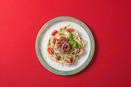 Photo pour Vue du dessus de la Pappardelle cuite aux tomates, basilic et prosciutto sur fond rouge - image libre de droit