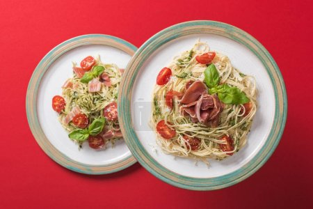 Photo for Top view of cooked Pappardelle with tomatoes, basil and prosciutto on plates on red background - Royalty Free Image