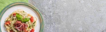 Photo pour Vue du dessus de la Pappardelle cuite aux tomates, basilic et prosciutto sur assiette sur serviette verte sur surface grise, vue panoramique - image libre de droit