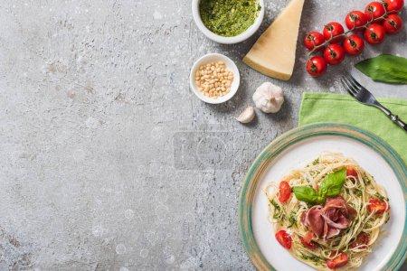 Draufsicht auf gekochte Pappardelle mit Tomaten, Basilikum und Prosciutto nahe Zutaten auf grauer Oberfläche