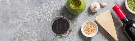 Photo pour Vue panoramique du Parmesan, des pignons, de l'ail, de la sauce pesto et du vin rouge sur une surface grise - image libre de droit