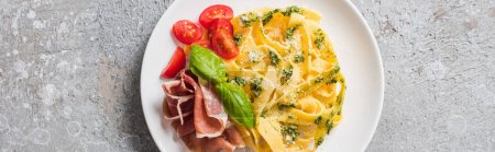 Photo for Top view of cooked Pappardelle with tomatoes, pesto sauce and prosciutto on grey surface, panoramic shot - Royalty Free Image
