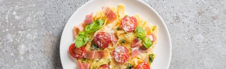 Photo pour Top view of cooked Pappardelle with tomatoes, pesto sauce and prosciutto on grey surface, panoramic shot - image libre de droit