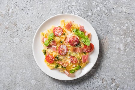 top view of cooked Pappardelle with tomatoes, pesto sauce and prosciutto on grey surface