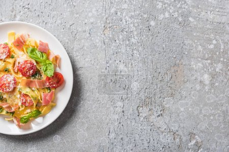 Photo for Top view of cooked Pappardelle with tomatoes, pesto sauce and prosciutto on grey surface - Royalty Free Image