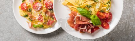 Photo for Selective focus of cooked Pappardelle with tomatoes, basil and prosciutto on plates on grey surface, panoramic shot - Royalty Free Image