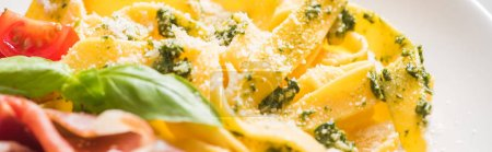 Photo for Close up view of delicious Pappardelle with tomatoes, Parmesan, pesto sauce, basil and prosciutto - Royalty Free Image