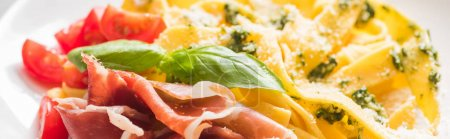 Photo for Close up view of delicious Pappardelle with tomatoes, Parmesan, pesto sauce, basil and prosciutto, panoramic shot - Royalty Free Image