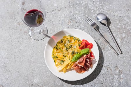 top view of tasty Pappardelle with tomatoes, pesto and prosciutto near red wine and cutlery on grey surface