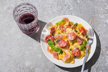 Photo for Top view of tasty Pappardelle with tomatoes, pesto and prosciutto with fork near red wine on grey surface - Royalty Free Image