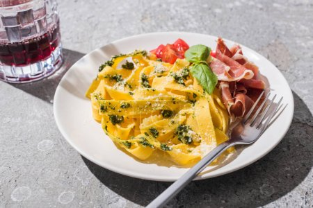 Photo for Tasty Pappardelle with tomatoes, pesto and prosciutto with fork near red wine on grey surface - Royalty Free Image