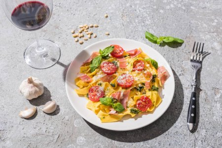 Pappardelle with tomatoes, pesto and prosciutto near red wine and ingredients on grey surface