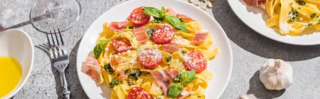 fresh Pappardelle with tomatoes, pesto and prosciutto near ingredients on grey surface, panoramic shot