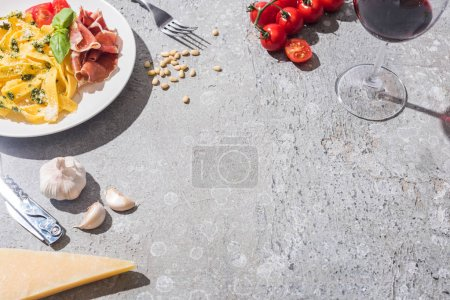 Photo for Fresh Pappardelle with tomatoes, pesto and prosciutto near red wine and ingredients on grey surface - Royalty Free Image