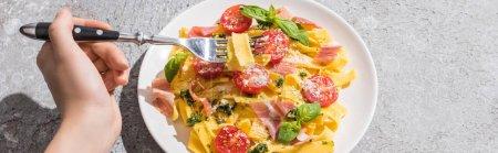 Photo pour Vue recadrée de la femme mangeant de savoureuses Pappardelle aux tomates, pesto et prosciutto à la fourchette sur surface grise, prise de vue panoramique - image libre de droit
