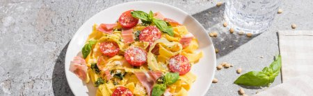 Photo for Tasty Pappardelle with tomatoes, pesto and prosciutto near water, napkin and pine nuts on grey surface, panoramic shot - Royalty Free Image