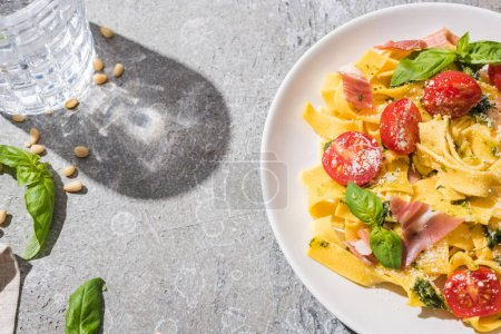 top view of tasty Pappardelle with tomatoes, pesto and prosciutto near water on grey surface