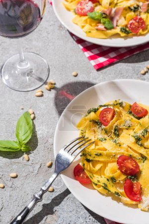Photo for Tasty Pappardelle with tomatoes, pesto and prosciutto with fork near red wine, basil and pine nuts on grey surface - Royalty Free Image