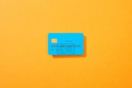 Foto de Vista superior de la plantilla de tarjeta de crédito azul en fondo naranja. - Imagen libre de derechos
