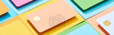Foto de Tarjetas de crédito vacías multicolores en fondo colorido, disparo panorámico. - Imagen libre de derechos