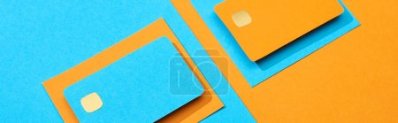 Photo pour Cartes de crédit vides colorées sur fond bleu et orange, panoramique - image libre de droit