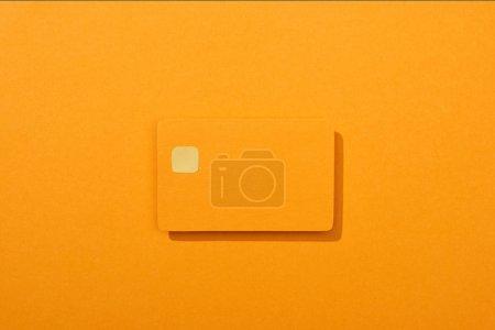 Photo pour Vue du dessus de la carte de crédit vide coloré sur fond orange - image libre de droit