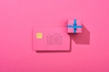 Photo for Top view of colorful empty credit card with gift box on pink background - Royalty Free Image