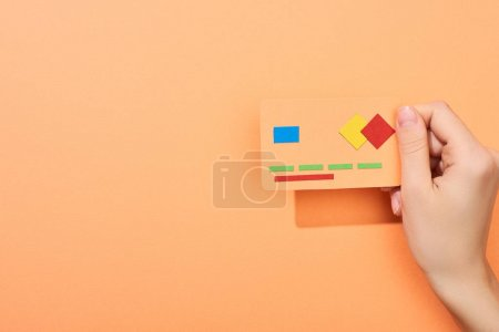 cropped view of woman holding credit card template on peach background