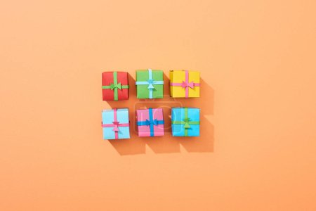 top view of multicolored small gift boxes on peach background