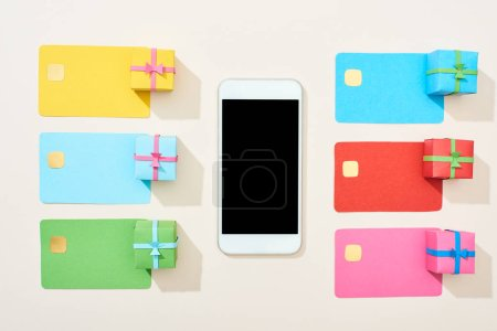 Photo for Top view of multicolored empty credit cards, smartphone and gift boxes on white background - Royalty Free Image