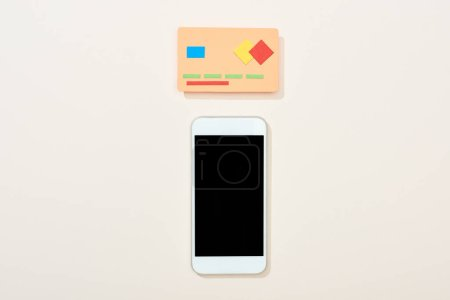 top view of empty credit card and smartphone on white background
