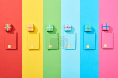 Photo for Top view of multicolored empty credit cards and gift boxes on rainbow background - Royalty Free Image
