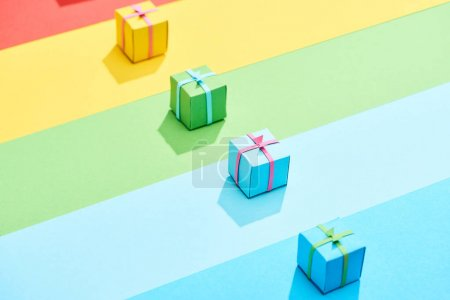 multicolored gift boxes on rainbow background
