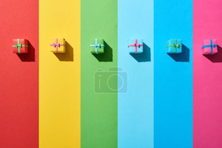 Photo for Top view of multicolored gift boxes on rainbow background - Royalty Free Image