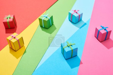 Photo for Multicolored gift boxes scattered on rainbow background - Royalty Free Image