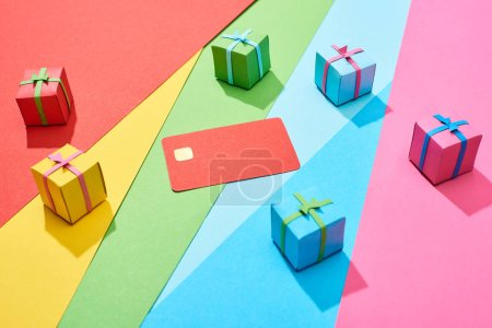 Photo for Red empty credit card and multicolored gift boxes on rainbow background - Royalty Free Image