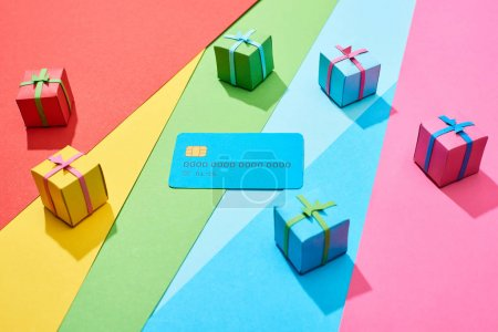 Photo for Empty credit card and multicolored gift boxes on rainbow background - Royalty Free Image