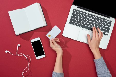 top view of credit card on red background with smartphone, laptop, earphones, coffee, notebook and plant
