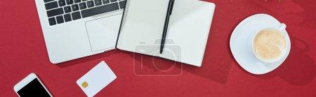 Photo pour Vue du dessus de la carte de crédit sur fond rouge avec smartphone, ordinateur portable, café, ordinateur portable avec stylo, vue panoramique - image libre de droit