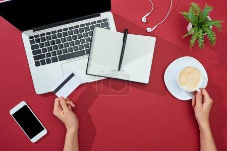 Photo pour Vue partielle de la femme tenant la carte de crédit et tasse de café près de smartphone, ordinateur portable, écouteurs, ordinateur portable et plante sur fond rouge - image libre de droit