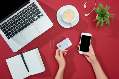 Photo for Partial view of woman holding credit card and smartphone near coffee, laptop, earphones, notebook and plant on red background - Royalty Free Image