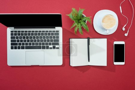flat lay with smartphone, laptop, earphones, coffee, notebook with pen and plant on red background